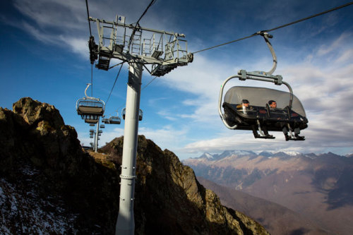 humanrightswatch:  Tourists take in views of the Caucasus Mountains from a chairlift at the newly-constructed Rosa Khutor Alpine Center ski resort in the Caucasus Mountains, which will host the alpine skiing events during the 2014 Winter Olympic and Paralympic Games in Sochi, Russia. © 2012 Brent Stirton/Reportage by Getty for Human Rights Watch