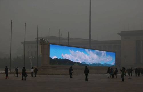 A bright video screen shows images of blue sky on Tiananmen Square during a time of dangerous levels of air pollution, on January 23, 2013 in Beijing.