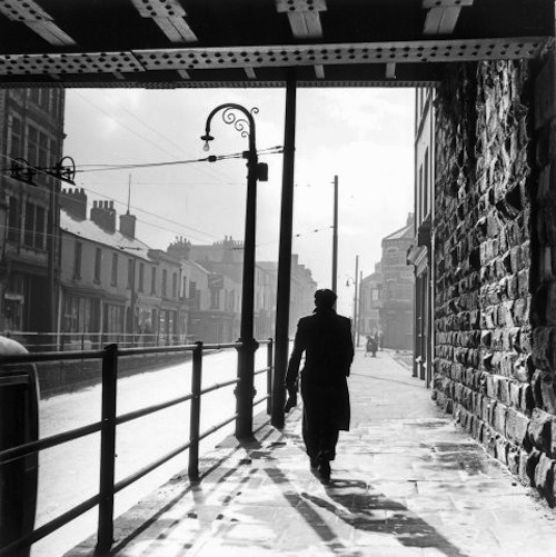 Bert Hardy Railway Walk. A man walking under a railway bridge in the dockland area of Cardiff, known as Bute Town or Tiger Bay, 1950s. From Bert Hardy/Getty Images