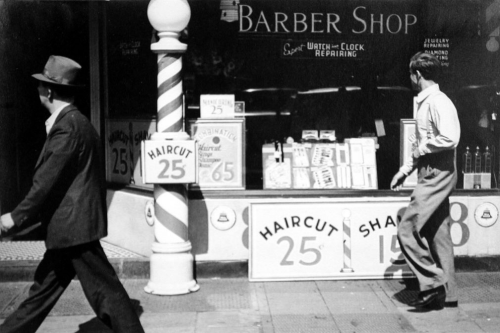 onlyoldphotography:  Rudy Burckhardt: Two Men Walking Past Barber Shop, New York City, ca.1939
