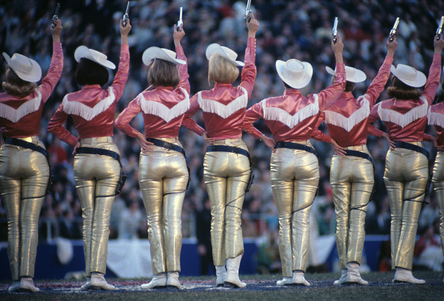 siphotos:  The Dallas Cowboys cheerleaders fire their guns in the air during game the 1967 NFL Championship between Green Bay and Dallas. (Neil Leifer/SI)