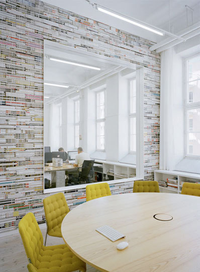 {Elding Oscarson designed this office for a design bureau for magazines and web. Besides having a literal relevance to the client's business, the wall made of stacked bundles of magazines is not only a natural conversation piece in its mere irrationality, but also works as an acoustical absorbent.}