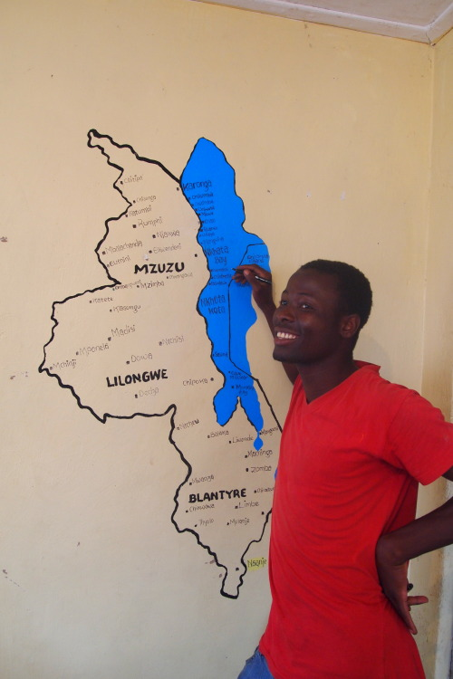 Kelvin painting a map of Malawi on my living room wall.
