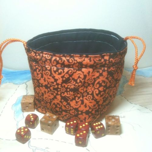 You will never lose your dice again. Orange Victorian Paisley Print dice bag by Greyed Out. Dice bag is lined in gray suede and fully reversible.