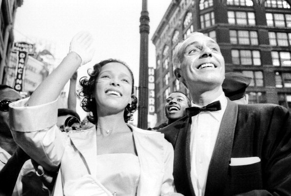 Dorothy Dandridge waving to her adoring fans at the June 26, 1959 world premiere of Porgy and Bess. Also pictured is her gold digging, con artist 2nd husband, JackASS Denison.