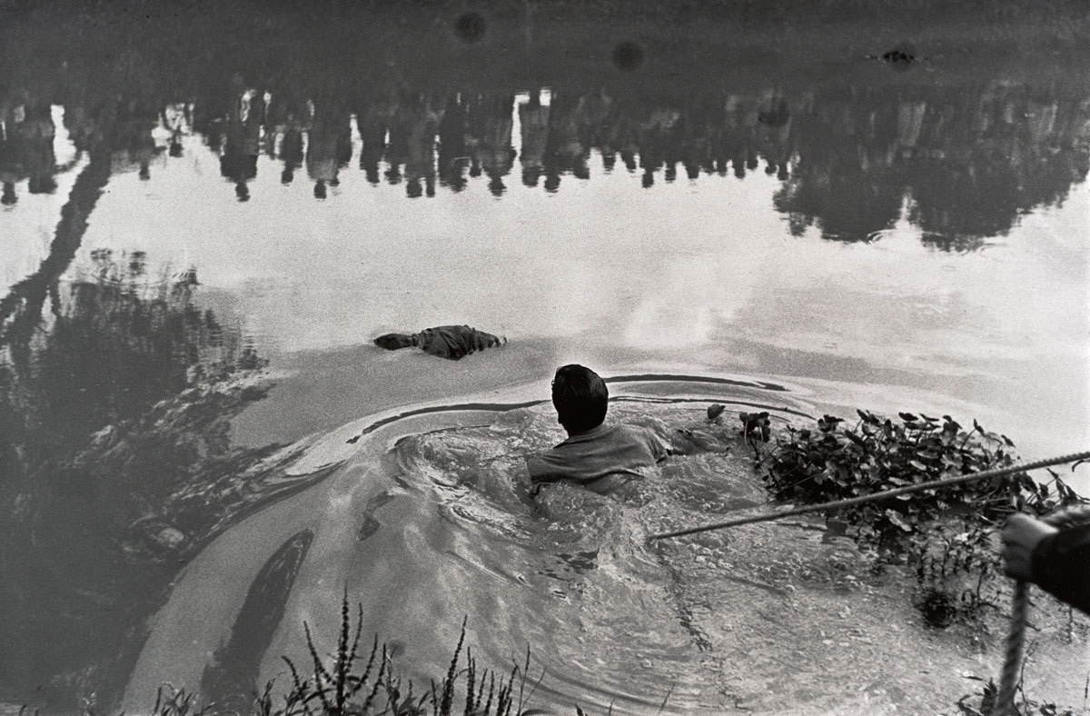 A man swims to recover a drowned boy. Look hard at the reflection.