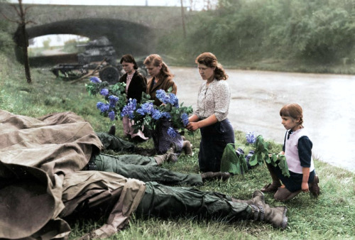 Russian women place flowers by the bodies of four American soldiers slain by German officers, 1945.