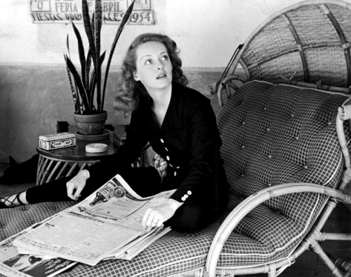 The top box-office star of Warner Bros., Bette Davis, skims through the morning newspapers in the playroom of her home. Photographed by Alfred Eisenstaedt, 1930's.