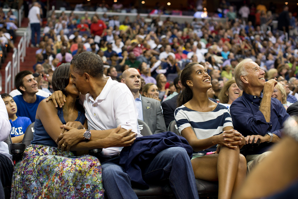 "July 16, 2012""The President and First Lady were attending the game between the U.S. Men's Olympic basketball team and Brazil in Washington, D.C. During the first half, the jumbotron flashed couples on their 'Kiss Cam', where they are then induced by the crowd to kiss each other. But neither the President or First Lady saw themselves when they were flashed on the 'Kiss Cam', and some in the audience booed when they didn't kiss. At halftime, as we walked to the locker room to visit the U.S. team, daughters Malia and Sasha were asking their parents why they hadn't kissed during their 'Kiss Cam' moment. Both the President and First Lady said they hadn't even realized what had happened and didn't know why people were booing. So in the second half, when they appeared again on the 'Kiss Cam', the President leaned over to kiss the First Lady amidst audience cheers as Malia and the Vice President watched overhead on the jumbotron."" (Official White House Photo by Pete Souza) Most iconic Pete Souza photos of Obama family's first 4 years in the White House"