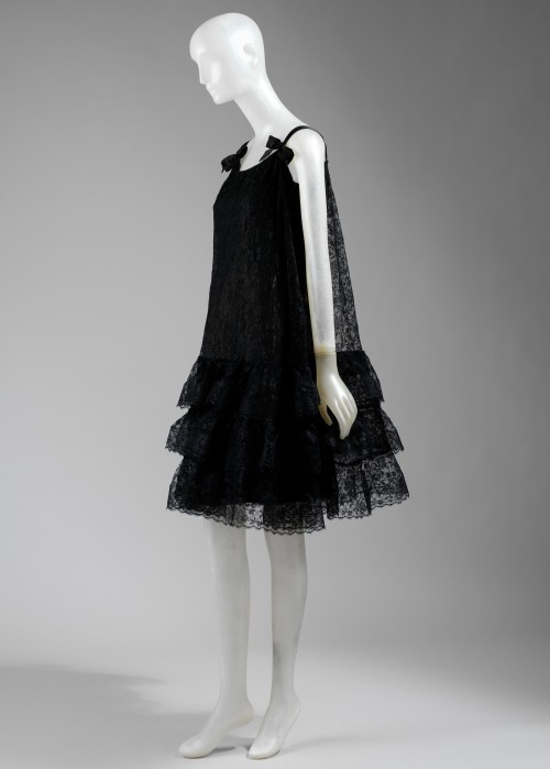 fashioninhistory:  Evening Dress Balenciaga Autumn/Winter 1965-66 This short evening dress of black lace consists of three layers. The first layer is a built-in bra supported by six bones, two in front and back, one at each side. The second layer is a slip of cream-colored silk with a sheer black chiffon overlay. The slip is shaped like a sheath and has a wide band of lace at the hem. The outer layer consists of a loose-fitting baby-doll dress with a triple tier of ruffles on the skirt. The dress has a boat neckline, and shoulder straps of black satin ribbon finished in bows. There is a zipper closure at the left seam.- The Metropolitan Museum of Art