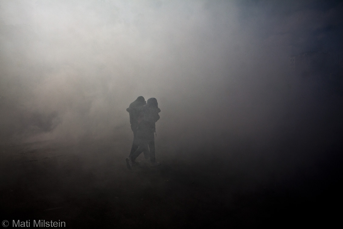 Fire and Smoke I  Palestinians walk through a cloud of smoke and tear gas during a protest near the West Bank city of Ramallah in support of Palestinian prisoners being held in Israeli detention.