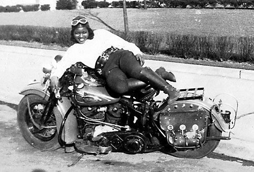 "hardcoregurlz:  The life and times of African-American motorcycling pioneer Bessie B. Stringfield seem like the stuff of which legends are made. In 1990, when the AMA opened the first Motorcycle Heritage Museum, Bessie was featured in its inaugural exhibit on Women in Motorcycling. A decade later, the AMA instituted the Bessie Stringfield Award to honor women who are leaders in motorcycling. And in 2002, she was inducted into the Motorcycle Hall of Fame.Bessie – BB as she was known among friends – would probably be amused and yet proud of all the attention. Referring to her adventures and her 60-plus years of riding, she once quipped: ""I was somethin'! What I did was fun and I loved it.""In the 1930s and 1940s, Bessie took eight long-distance, solo rides across the United States. Speaking to a reporter, she dismissed the notion that ""nice girls didn't go around riding motorcycles in those days."" Further, she was apparently fearless at riding through the Deep South when racial prejudice was a tangible threat. Was Bessie consciously championing the rights of women and African-Americans? Bessie would most likely have said she was simply living her life in her own way.In interviews for Hear Me Roar, Bessie revealed how she drew courage from two things: Her Catholic faith in Jesus Christ, whom she called ""The Man Upstairs,"" and the values she learned from her adoptive mother.Early on, Bessie had to steel herself against life's disappointments. Born in Kingston, Jamaica in 1911, as a child she was brought to Boston but was orphaned by age 5.""An Irish lady raised me,"" she recalled. ""I'm not allowed to use her name. She gave me whatever I wanted. When I was in high school I wanted a motorcycle. And even though good girls didn't ride motorcycles, I got one.""She was 16 when she climbed aboard her first bike, a 1928 Indian Scout. With no prior knowledge of how to operate the controls, Bessie proved to be a natural. She insisted that the Man Upstairs gave her the skills.""My [Irish] mother said if I wanted anything I had to ask Our Lord Jesus Christ, and so I did,"" she said. ""He taught me and He's with me at all times, even now. When I get on the motorcycle I put the Man Upstairs on the front. I'm very happy on two wheels.""She was especially happy on Milwaukee iron. Her one Indian notwithstanding, Bessie said of the 27 Harleys she owned in her lifetime, ""To me, a Harley is the only motorcycle ever made.""At 19, she began tossing a penny over a map and riding to wherever it landed. Bessie covered the 48 lower states. Using her natural skills and can-do attitude, she did hill climbing and trick riding in carnival stunt shows. But it was her faith that got her through many nights.""If you had black skin you couldn't get a place to stay,"" she said. ""I knew the Lord would take care of me and He did. If I found black folks, I'd stay with them. If not, I'd sleep at filling stations on my motorcycle."" She laid her jacket on the handlebars as a pillow and rested her feet on the rear fender.In between her travels, Bessie wed and divorced six times, declaring, ""If you kissed, you got married."" After she and her first husband were deeply saddened by the loss of three babies, Bessie had no more children. Upon divorcing her third husband, Arthur Stringfield, she said, ""He asked me to keep his name because I'd made it famous!""During World War II, Bessie worked for the army as a civilian motorcycle dispatch rider. The only woman in her unit, she completed rigorous training maneuvers. She learned how to weave a makeshift bridge from rope and tree limbs to cross swamps, though she never had to do so in the line of duty. With a military crest on the front of her own blue Harley, a ""61,"" she carried documents between domestic bases. Bessie encountered racial prejudice on the road. One time she was followed by a man in a pickup truck who ran her off the road, knocking her off her bike. She downplayed her courage in coping with such incidents. ""I had my ups and downs,"" she shrugged.In the 1950s, Bessie bought a house in a Miami, Florida suburb. She became a licensed practical nurse and founded the Iron Horse Motorcycle Club. Disguised as a man, Bessie won a flat track race but was denied the prize money when she took off her helmet. Her other antics – such as riding while standing in the saddle of her Harley – attracted the local press. Reporters called her the ""Negro Motorcycle Queen"" and later the ""Motorcycle Queen of Miami."" In the absence of children, Bessie found joy in her pet dogs, some of whom paraded with her on her motorcycle.Late in life, Bessie suffered from symptoms caused by an enlarged heart. ""Years ago the doctor wanted to stop me from riding,"" she recalled. ""I told him if I don't ride, I won't live long. And so I never did quit.""Before she died in 1993 at the age of 82, Bessie said, ""They tell me my heart is three times the size it's supposed to be."" An apt metaphor for this unconventional woman whose heart and spirited determination have touched so many lives. She was inducted into the Motorcycle Hall of Fame in 2002. – Ann Ferrar"