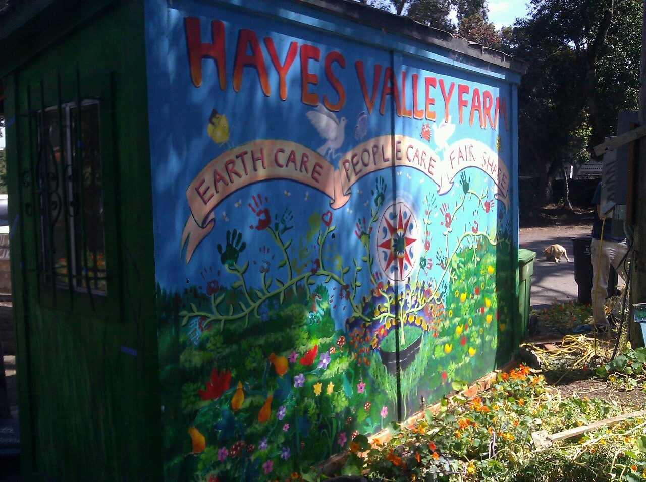Hayes Valley Farm's iconic mural displays the three ethics of permaculture - Earth Care, People Care, and Fair Share, as well as the many hands of core volunteers, painted in 2010 by Daniel Farnan.