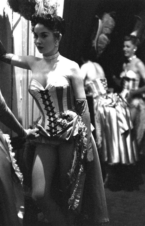 vintagechampagnefever:  Showgirls wait behind the stage curtain