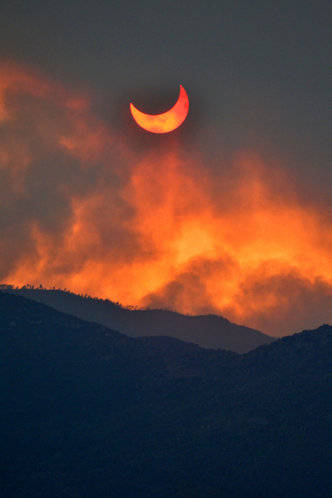 evocates:  Annular eclipse seen through smoke from the Arizona wild fires (by lissagwen)