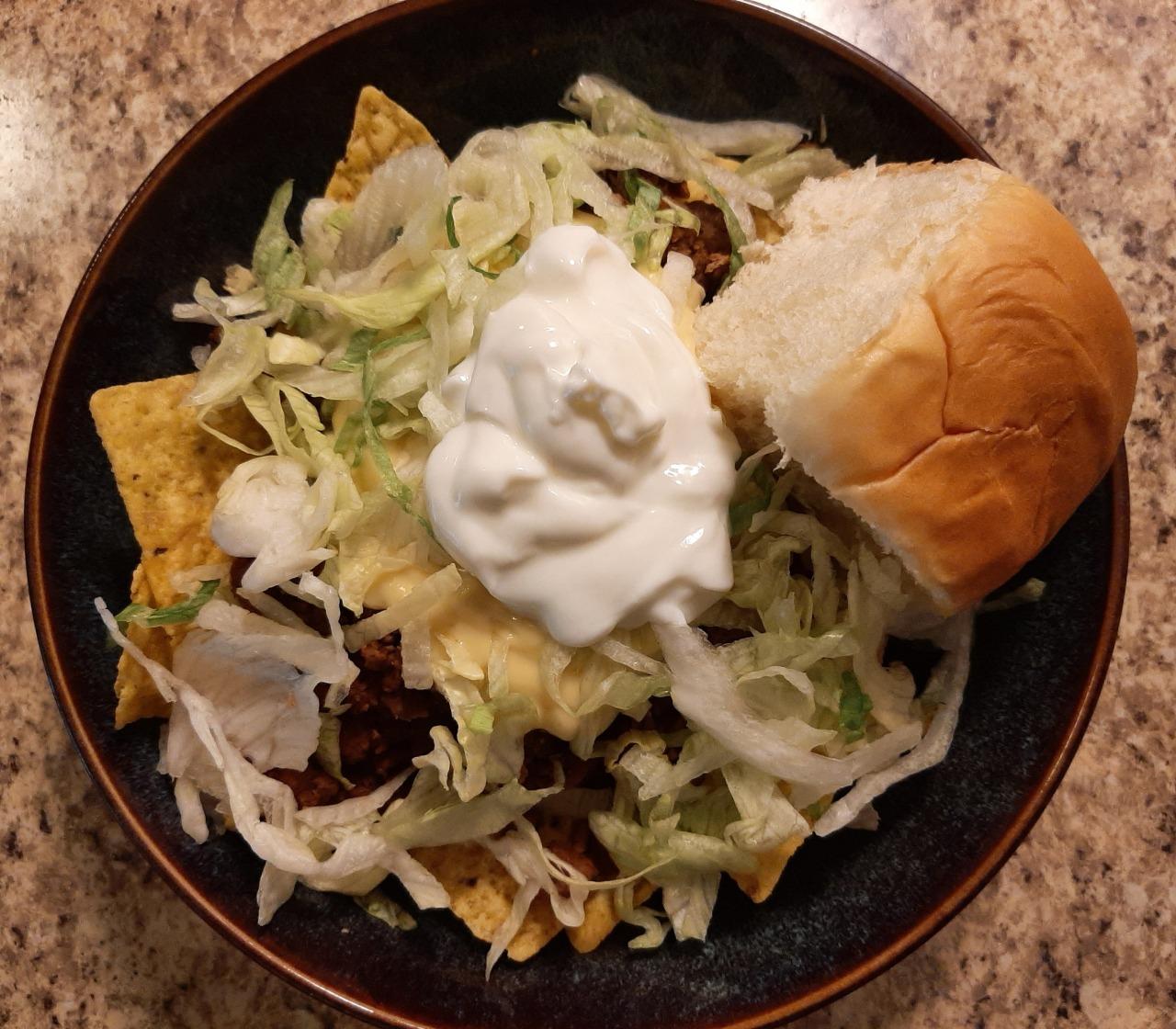 Nachos with taco-seasoned veggie meat, nacho cheese, shredded lettuce, sour cream, & a Hawaiian sweet roll #food#nachos#tortilla chips#veggie meat#quorn#taco seasoning#nacho cheese#cheddar#cheese#jalapeno#lettuce#sour cream#roll #hawaiian sweet roll #june#2021#june 2021#summer#vegetarian
