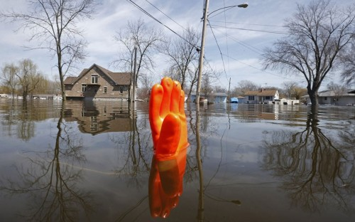 inothernews:  ORANGE ALERT   A rubber glove, used as a marker, bobs in floodwaters in Fox Lake, Illinois.  More snow and rain threaten to exacerbate flooding conditions in the Midwest from Oklahoma through Michigan, which has led to at least three deaths.  (Photo: Jim Young / Reuters via The Telegraph)  Spring floods. Bad urban planning. Nothing ever changes…