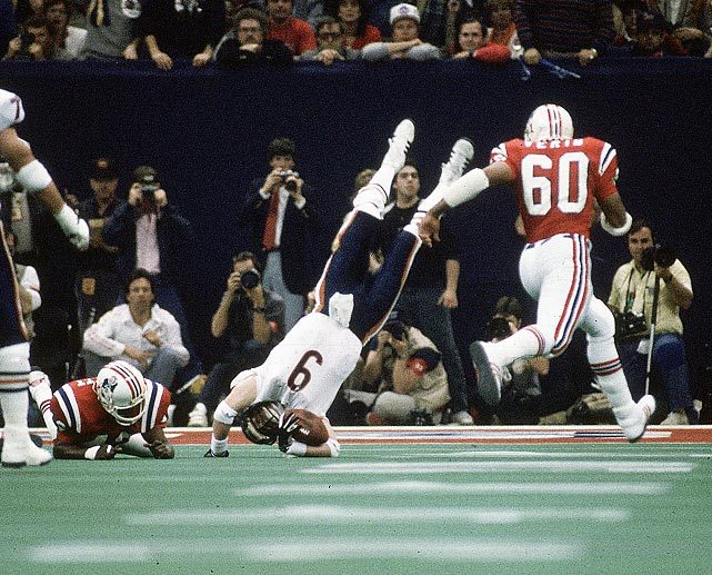 Chicago Bears quarterback Jim McMahon is upended on a scramble by the New England Patriots defense. McMahon became the first quarterback to rush for two touchdowns in a Super Bowl; he threw for 256 yards in the 46-10 rout. (Andy Hayt/SI) GALLERY: SI's 100 Best Super Bowl Photos