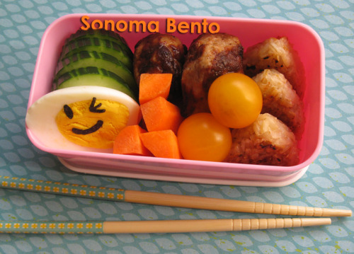 Smiley hard boiled egg bento with cukes, carrots, teriyaki chicken meatballs, yellow cherry tomatoes, and yaki onigiri. Read more on my bloggy blog.