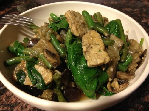 Tempeh and Vegetable Stir-Fry Steam one cubed eggplant 8-9 minutes. Meanwhile… sauté thinly sliced tempeh (I used organic three grain tempeh, which has a great texture) and minced garlic together in a small amount of olive and sesame oils in a wok, until lightly brown on both sides.  Add mushrooms, string beans and eggplant.  Sauté a few more minutes with liquid aminos (or soy sauce or substitute).  Top with several handfuls of fresh spinach and cover the wok for a minute or two.  When spinach wilts, stir everything together and serve over brown rice, optional.