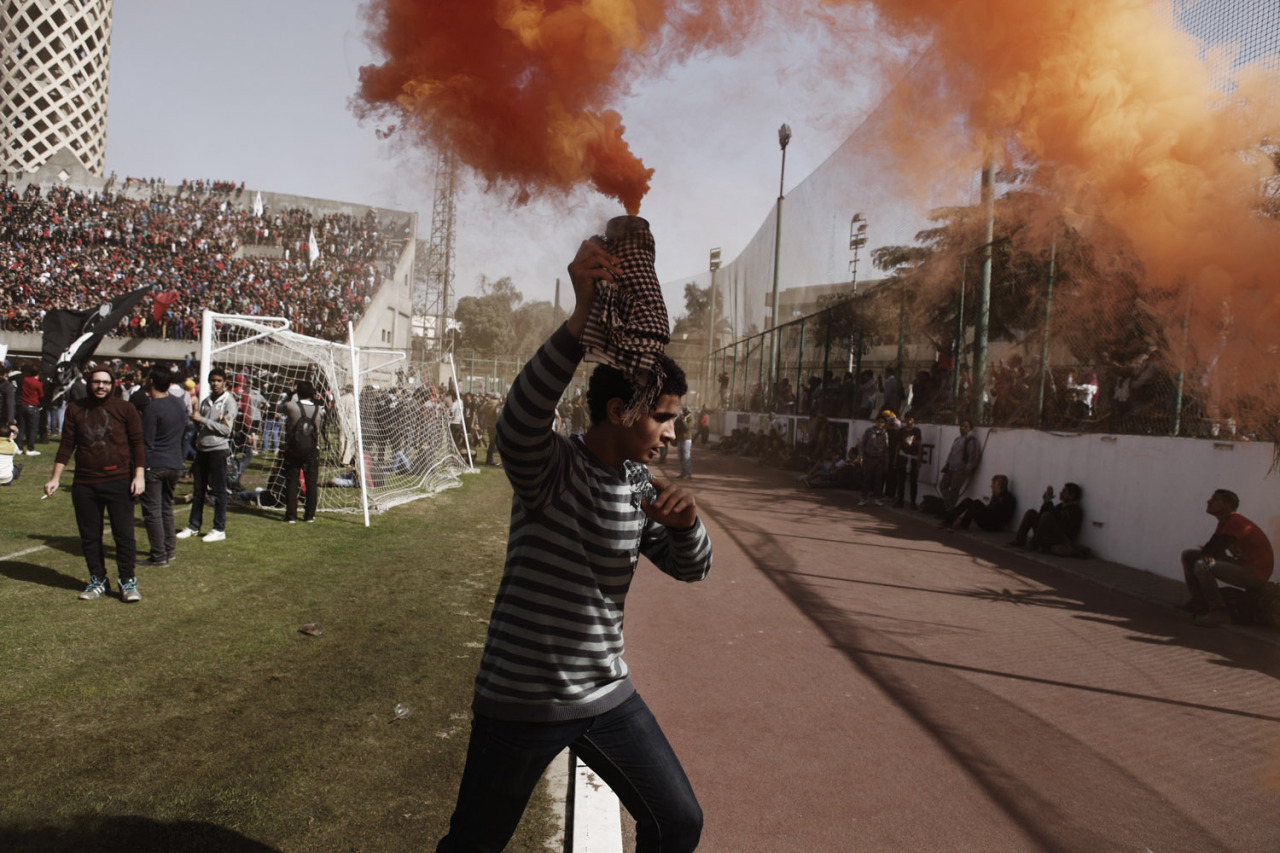 Jan. 26, 2013. An Egyptian soccer fan holds a smoke flare above his head in celebration after learning that 21 fans of the Al Masry football club, involved in a football stadium massacre last year, were sentence to death, in Cairo, Egypt. (Photo: Ed Giles—Getty Images) See more of the week's best images at TIME LightBox