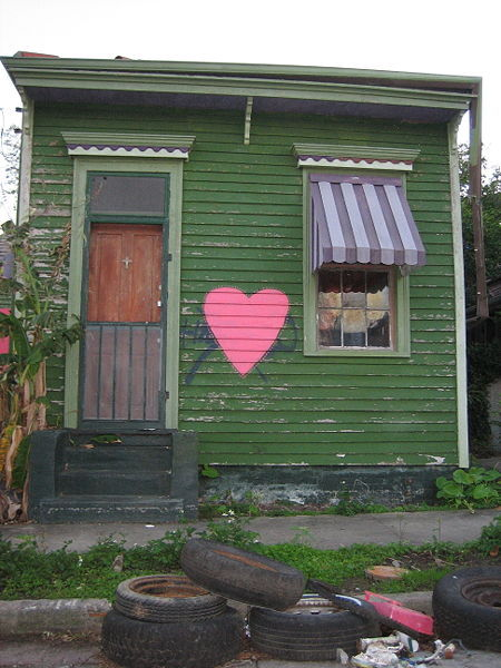 "Some people have asked me what a ""shotgun"" house is: http://en.wikipedia.org/wiki/Shotgun_house A ""shotgun house"" is a narrow rectangular domestic residence, usually no more than 12 feet (3.5 m) wide, with rooms arranged one behind the other and doors at each end of the house. It was the most popular style of house in the Southern United States from the end of the American Civil War (1861–65), through the 1920s. Alternate names include ""shotgun shack"", ""shotgun hut"" and ""shotgun cottage"". A railroad apartment is somewhat similar, but has a side hallway from which rooms are entered (by analogy to compartments in passenger rail cars)."