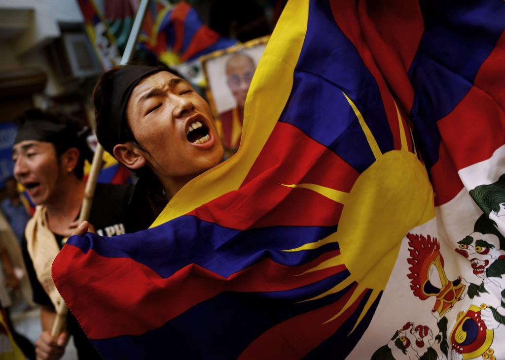fotojournalismus:  An exiled Tibetan holds a Tibetan flag as he shouts slogans during a protest at a local neighbourhood after they were stopped from protesting near the venue where Chinese Premier Li Keqiang was attending a meeting in New Delhi, India on May 20, 2013. [Credit : Kevin Frayer/AP]