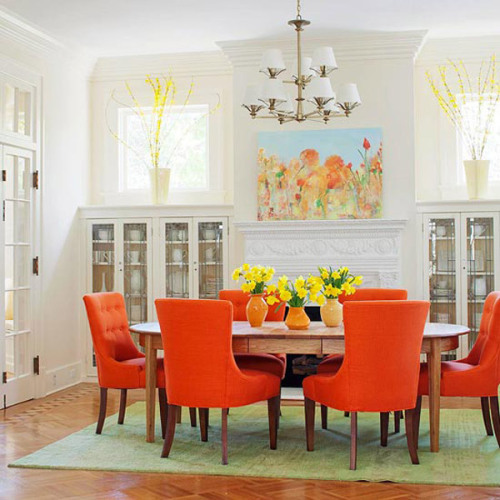 designed-for-life:  Colourful Dining Room Inspiration - Orange  Orange is a good color for a dining room as it has been associated with sociability and stimulation of appetite. Against a neutral backdrop, in this case white, the orange shades come alive. Also noteworthy is the choice of a light green rug. Certain shades of green are a close complementary color to orange, therefore it is a perfect partner to pair with orange. It counteracts it, thus creating a sense of balance in the room. The result is a lively, inviting space.  image via: http://www.bhg.com/decorating/color/paint/orange-home-decorating-ideas/#page=1