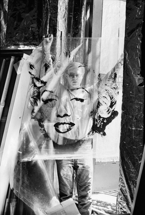 "forgetcity:  Andy Warhol with an unrolled acetate of ""Marilyn"" at the Factory, 1964."