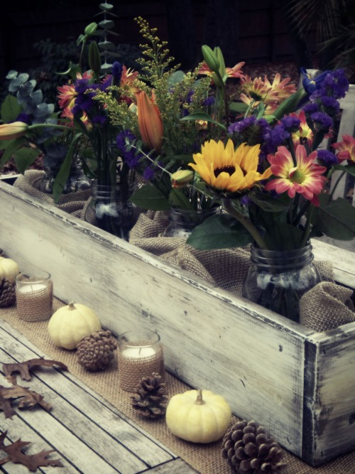 Fall flowers tucked into mason jars, wrapped with burlap, and tucked into the table top.