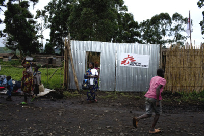 "Photo: An MSF clinic in Kitchanga, North Kivu. DRC 2009 © Michael Goldfarb DRC: North Kivu Fighting Damages Health Structures and Displaces Thousands Amid fighting in the town of Kitchanga in the east of the Democratic Republic of Congo (DRC), which has caused widespread casualties and damage to health facilities, the international medical humanitarian organization Doctors Without Borders/Médecins Sans Frontières (MSF) is mobilizing medical resources to the affected area, the organization said today. More than 55 civilians have reportedly been killed in the fighting, and 135 people wounded. Shelling also struck St. Benoit Hospital in Kitchanga today, killing two people and wounding eight. Many homes and other buildings have been burned, including the MSF compound. Thousands of civilians have fled. ""We call upon all parties to the conflict to respect the neutrality of health structures,"" said Hugues Robert, MSF's head of mission for North Kivu province. ""MSF is very concerned about the plight of civilians during intense periods of fighting like this. All parties to the conflict should not harm the population."" Several MSF Congolese staff members were displaced from their homes by the fighting, and widespread panic and fear is gripping the population as tensions between communities in the region escalate. Reaching Kitchanga is extremely difficult. An MSF surgeon, anesthetist, nurse, and emergency logistician arrived by helicopter yesterday to provide additional support to an MSF medical team based in the town. Dressing kits, surgery kits, medicine, plastic sheeting, and tents were also delivered. Several wounded people were also transferred to the North Kivu town of Mweso and to the provincial capital, Goma, for further treatment."
