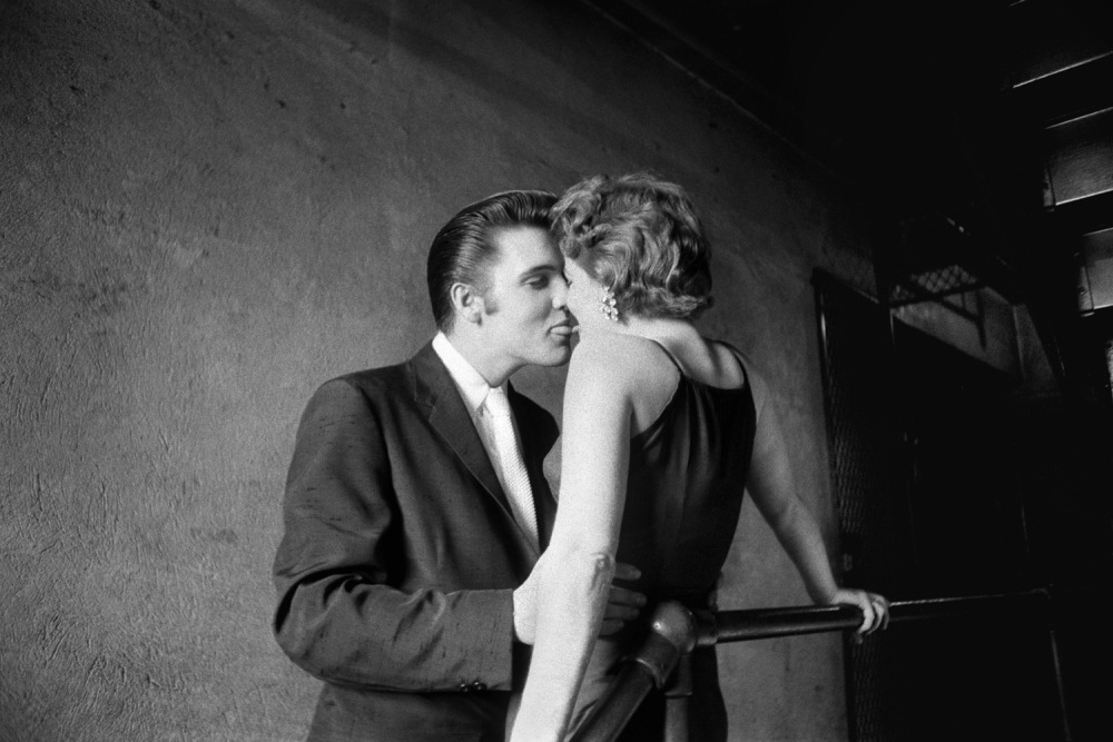 "No photographer would ever get as close to Elvis as Alfred Wertheimer. His intimate photographs of the young, rising star reveal a carefree and innocent time before he became a cultural icon. On the publication of Taschen's new book, Elvis and the Birth of Rock and Roll, TIME met with Wertheimer to reminisce about the days and nights he spent with the rocker on the cusp of unfathomable fame: http://ti.me/Z5FfTe  Wertheimer talks about his iconic picture, 'The Kiss': June 30, 1956. Backstage at the Mosque Theatre, Richmond Virginia. The story on this one is that Elvis had performed somewhere near Charleston, South Carolina on one of those one-day affairs. So Elvis was back in his hotel room. She was with some of her friends, slightly inebriated, when her friends said, ""we dare you to call Elvis at his hotel."" So she gets on the phone and she's showing the gals that she's got chutzpah and says, ""Are you Elvis Presley?"" He says, ""Yes, I am."" At the time, her name was Bobbi Owens, so he says, ""That's nice Bobbi,"" and they get into a half an hour chat. Elvis says, ""The next time I'm down in this area I'll send a car for you and you can come up and be with me all day and watch from backstage."" So she said ""okay.""A while later, maybe a month or so, he's performing at the Mosque theater, and so he calls her and says ""I'll be there on the 30th of June, can you make it?"" So he has one of his bodyguards drive from Memphis (400 miles) down to South Carolina, pick her up and go up to Richmond (that's almost a 1000 miles round trip). And Elvis meets her at the hotel, and they horse around a little bit at the hotel.  Then he takes her to the theater in the back of the cab with 'Junior' Smith. After Elvis finishes combing his hair above the stage (there were no dressing room in the theater) he disappeared on me. I looked around to find Elvis, so I walk down the stairwell… and I see two figures at the end of the hallway, with a light over their head and a bulb in the background. And I'm standing here, I become a human tripod… I'm shooting stuff at a half a second, and I'm thinking about what Capa said, that if you aren't close enough, your photos are probably boring…so I try and get up on top of these pipes and shoot over her shoulder Hollywood style into her face. What I needed was front lighting. So I'm going down on the landing and I've got my front lighting, and no sooner do I get myself set, then she says to him, ""Elvis, I bet you can't kiss me!"" That's all he needed, so he said, ""I betcha I can."" I didn't realize that he had tried twice to kiss her until about two weeks later. Until I developed my film in my laboratory, I didn't realize he had bent her nose the first time, and the second time it was perfect, tongue to tongue, tip to tip. 55 years later, she denies on national television that he ever did kiss her, and that she was really on her way to Philadelphia to see her boyfriend.  For more of Wertheimer's images and memories of Elvis, visit LightBox."