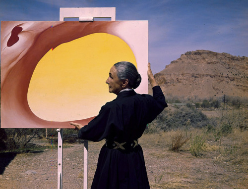 Photograph of artist Georgia O'Keeffe in the desert with one of her paintings. TONY VACCARO/GEORGIA O'KEEFFE MUSEUM
