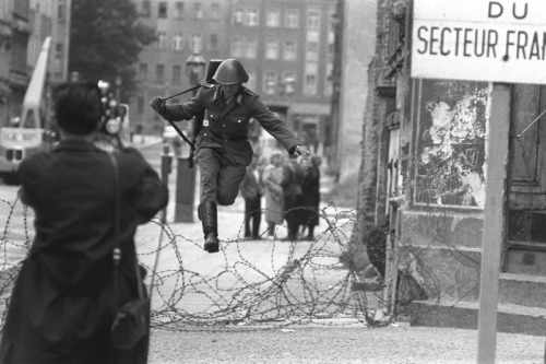 This photo was taken by Peter Leibing when an East Germany soldier named Conrad Schumann which guard the construction of the Berlin Wall defected to the West Berlin by jumping over the barbed wire that separated the West and East Berlin . For years this photo had been an iconic symbol of the cold war era . After his defection , there were also several people that tried to defect to the West Berlin but unfortunately many of them were shot dead by the border guards . Their defection showed the world the economic prosperity and social freedom of the West Berlin ( West Germany ) in comparison to the East Berlin or East Germany .