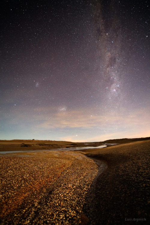 "Milky Way from the Ocean Floor      Word from the photographer: ""This photo is taken from the seabed while the tide was low.      At this place in the Argentinian patagonia the tide is 7-8 meters high. It will be covered by several meters of water a few hours after the shot. The Magellanic clouds can be seen at the left of the Milky Way where the coalsack nebula can be seen as a dark patch against the sky.      The bright star Canopus is seen reflected in a tidal pool near the horizon. The wet shells in the ocean floor reflect the light of the stars."" — Luis Argerich"