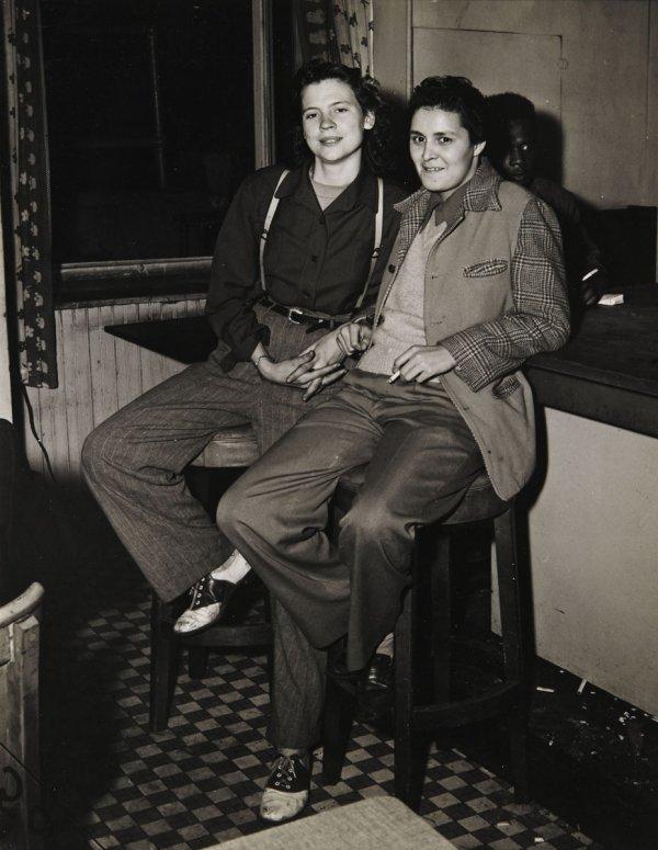 "queermuseum:  Weegee, ""Girls at the Bar,"" 1946. This image was captured by photojournalist Weegee in Greenwich Village and originally published in his book The Naked City. While the Village became notorious as a lesbian gathering place by the 1920s, it is often associated with middle-class feminism and groups such as The Heterodoxy Club. This photo instead reflects a working class, possibly racially integrated space, which was less likely to be documented by mainstream journalists.  The placement of the women's hands is deceiving and while they are not holding hands, their body language and expressions suggests a closeness as well as a comfortability with themselves and their surroundings. While wearing pants and clothing associated with men became more acceptable for women during World War II, to go out in public in such outfits at the time was still a bold decision. As Alan Berubé argues in his book Coming Out Under Fire, World War II played a crucial role in the creation of gay and lesbian communities, in coastal cities specifically, bringing together men and women from all over the country who were able to enact new types of relationships away from the prying eyes of their families and neighbors. This photo captures the end of this era before the postwar turn to McCarthyism and its virulent homophobia made life for the ""girls at the bar"" even more repressive.  -Cookie"