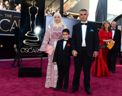 themindislimitless:  badassmuslimahs:  Emad Burnat and his wife Soraya representing Palestine (Nominated for '5 Broken Cameras') at the Oscars. Soraya is wearing a traditional Palestinian Thob.  They were also completely disrespected by us customs officials and detailed in complete isolation for several hours, where he was treated like dirt and told he was going to be deported back to Palestine. He even showed them the invitation to the ceremony, but they didn't believe him. Eventually he contacted Michael Moore, who got help and got him released. Read about it. I just wanted to note that as a reminder that even people nominated for Oscars get treated that way. Unsurprising, unfortunately, and utterly disgusting.