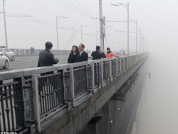 polishmaid:  A newspaper photographer was trying to take a picture of the fog looking over Wuhan Yangtze River in Wuhan, at Hubei province in China.In the background you will notice a body falling. It unbelievable how so many words a photo can say. People getting on with their lives, cars driving past and someone so low in their lives they feel they need to take their own and it going unnoticed it happening by the rest of the world