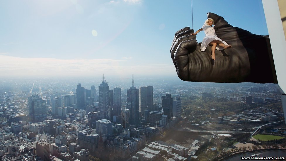Stunt expert Leigh-Anne Vizer sits on King Kong's hand above the Australian city of Melbourne during a King Kong production photo call at Eureka Skydeck.