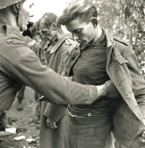 Captured German soldiers being searched by Canadian soldiers.