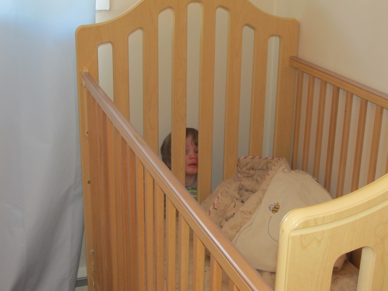 Not quite sure how he got between the crib and the wall, but he sure wasn't happy about it.