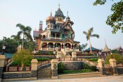 On May 17th, Mystic Manor, a high-tech dark ride, will officially open as the center attraction in the newly developed Mystic Point in Disneyland Hong Kong. Mystic Point is one of the three new land expansions the park has been developing over the past four years, and has been described as a site that is located in the middle of a dense forest riddled with supernatural and magical forces. Mystic Manor serves as the home to Lord Henry Mystic, a member of the Society for Adventurers and Explorers, and his monkey Albert. The aged explorer owns a variety of exotic artifacts, including an enchanted music box that Albert opens at the start of the ride, causing all of the artifacts in the house to come to life.  Below is a link to a video featuring the full ride through for Mystic Manor.  Technical aspects of the attraction include a trackless ride system, advanced Audio-Animatronic figures, and a stunning repertoire of other visual affects.  Note: Mystic Manor is not intended to be a version of The Haunted Mansion.  Video: Full Ride through Mystic Manor