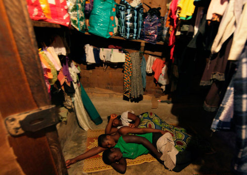 Teenage Kayayo girls sleep at a market in Accra, Ghana. The Kayayei ('market girls') move from northern Ghana, where sustenance is hard to come by, to Accra in search of work. They often face difficult labor and dangers such as robbery and kidnapping. For many Kayayei, the journey south signals an affirmation of adulthood, and a transition between tradition and modernity. From Kayayo Girls of Ghana, by Veronique de Viguerie
