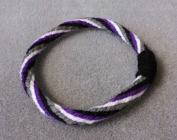 lexlexington:  Kumihimo braided bracelet in the asexual pride flag colours. Made with yarn.  at first it looks like a quality rubber band for the common ponytail. If only that were the case.
