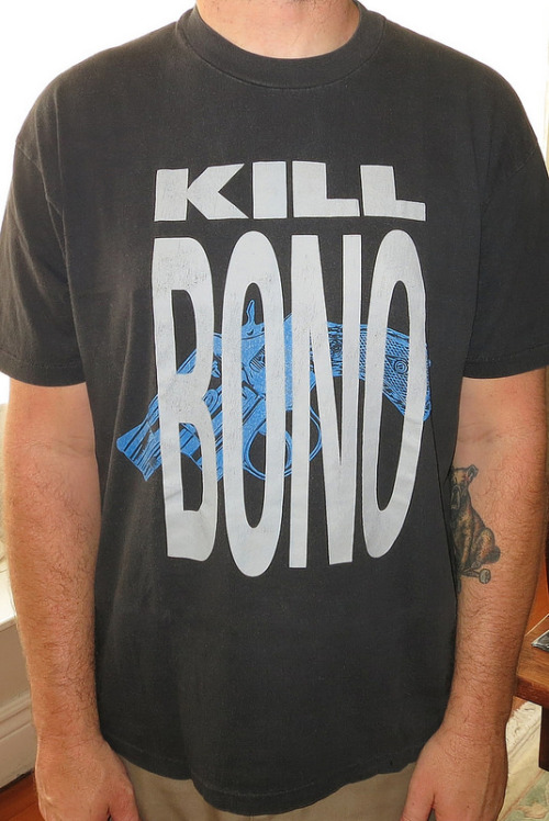 """Day: 1083 Shirt: Negativeland / SST - Kill Bono Color: Black Brand: Hanes Heavyweight Source: I bought this from an SST mail-order catalog back in the day. no reason i don't want Bono dead but i certainly wasn't a fan of U2 at the time, or now for that matter. but as someone pointed out today its a shirt that was made in response to the experimental band Negetiveland's """"u2"""" ep.  I Still Haven't Found What I'm Looking For (1991 a cappella mix) by Negativland on Grooveshark A real balsy maneuver on Negativeland's behalf using all these samples and not giving one fuck at all.   that album was supposedly put out as kind of a big FU to the popularity of U2 and the album cover was made to look like a new U2 album as well. OBVIOUSLY they got the shit sued out of them and that album art above is now long out of print and really rare.  I Still Haven't Found What I'm Looking For (special edit radio mix) by Negativland on Grooveshark so they renamed the ep the """"Guns"""" ep and changed the art to this and thus you can see how the volition of a shirt design has become.   It's all really quite interesting really. the whole scenario, like the fact that Greg Ginn put this out on SST, the fact that this is totally indicative of 1991 weird trippy shit form people who clearly listened to a lot of Dead Kennedys. the art debacle and most of all listening to KC Kasem ranting off much talking about """"who give s a shit about U2 band members because no one will give a shit anyway, for Christ's sake that are from England!"""" Listen to both songs i assure you you will find it interesting. and if you love this shirt I'm pretty sure good 'ol Greg is still capitalizing off this design today is his crappy SST Superstore."""
