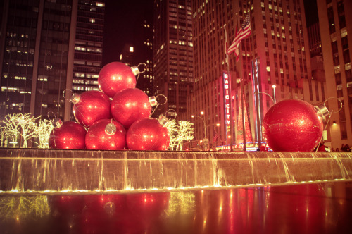"Giant red ornaments. 6th Avenue. Midtown holiday decorations. New York City   Every single year, my love of New York City holiday decorations is hard to hide. I eagerly wait for December because I know that Rockefeller Center and surrounding areas of midtown Manhattan will be dolled up in their holiday finest. Tree branches are entirely ensconced with holiday lights, giant ornaments sit stop golden fountains and even street food vendors go out of their way to accessorize their food stands with holiday decorations.  This display close to Rockefeller Center is one of my favorites. It's a New York City holiday decoration extravaganza. It sits across from Radio City Music Hall (home of the Rockettes and Radio City Christmas Spectacular) on 6th Avenue and is absolutely gorgeous at night. Giant red ornament balls sit on a fountain which is surrounded by trees ensconced in holiday lights.  Happy holidays everyone!!   —-  View this photo larger and on black on my Google Plus page  —-  Buy ""Giant Red Ornaments on 6th Avenue - Midtown Holiday Decorations - New York City"" Posters and Prints here, email me, or ask for help."