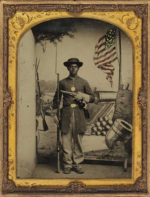 "street-popper:  Freedom Fighter | 1865 by Black History Album on Flickr.  The gauntlets and pistol are likely the photographer's props.  An infantry soldier would not be likely to wear leather cavalry gloves, as it would make it difficult to grasp a cartridge and nearly impossible to procure a cap from his cap pouch.  He also doesn't have a holster for the pistol, and again, a Union infantryman would not be issued a pistol, nor likely to carry one because of its weight.   The image is reversed, and he is holding the rifle at ""order arms"" with his left hand which is probably why it looks uncomfortable, as he would have been used to it being on his right.  The cap pouch and cartridge box would be on his right side."