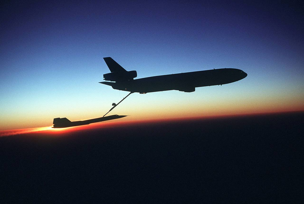 A right side view of a KC-10 Extender aircraft refueling an SR-71 Blackbird aircraft in-flight during testing. The Extender, silhouetted against the sunset horizon, is from the 78th Air Refueling Squadron, and the Blackbird, the 9th Strategic Reconnaissance Wing. Shot August 2nd, 1981.  Yep.