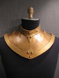Bronze colored leather gorget from http://www.osfcostumerentals.org/stock/Accessories/Gorgets/slides/11000917%20Gorget%20gold%20bronze%20leather.html