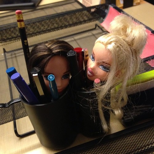 Bratz doll heads in a pencil holder. Idk.